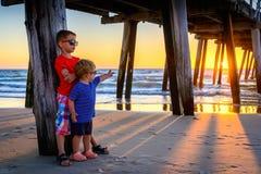 Мальчики стоя на пляже под пристанью на заходе солнца Стоковые Фото