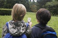 Мальчики с рюкзаками используя компас стоковые изображения rf