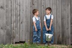 Мальчики с щетками и краска на старой стене Стоковые Изображения RF