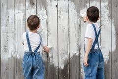 Мальчики с щетками и краска на старой стене Стоковые Изображения