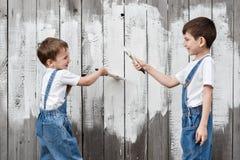 Мальчики с щетками и краска на старой стене Стоковая Фотография RF