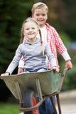 Мальчик давая езду девушки в тачке Стоковые Изображения RF
