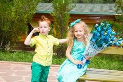Мальчик дает цветок к ребенку девушки на с днем рождения Концепция торжества и детство, влюбленность Стоковые Фото