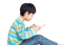 Мальчик Азии используя цифровую таблетку стоковые изображения