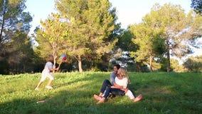 Мальчик бежать вокруг его родителей в парке сток-видео