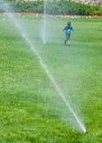 Мальчик бежать вокруг спринклеров воды Стоковые Изображения