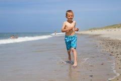 Мальчик бежать и усмехаясь на пляже стоковое фото rf
