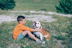 Мальчик бежать на поле с собакой быка в горах Стоковые Изображения RF