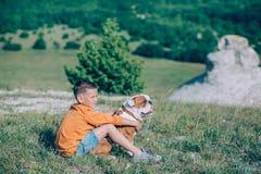 Мальчик бежать на поле с собакой быка в горах Стоковое Изображение