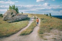 Мальчик бежать на поле с собакой быка в горах Стоковая Фотография RF