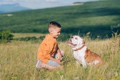 Мальчик бежать на поле с собакой быка в горах Стоковая Фотография