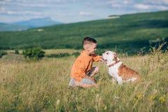 Мальчик бежать на поле с собакой быка в горах Стоковое Изображение RF