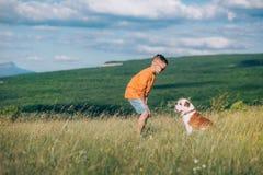 Мальчик бежать на поле с собакой быка в горах Стоковые Фотографии RF