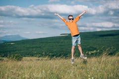 Мальчик бежать на поле с собакой быка в горах Стоковое Фото