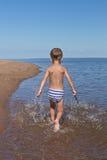 Мальчик бежать через воду Стоковая Фотография RF