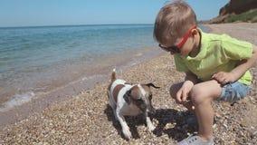 Мальчик бросает камни для того чтобы выследить на море акции видеоматериалы