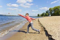 Мальчик бросает песок на пляже Стоковые Изображения
