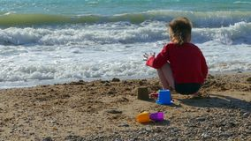 Мальчик бросает песок на пляже видеоматериал