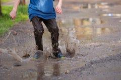 Мальчик брызгая в лужице грязи, Стоковое Изображение