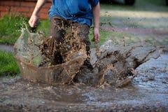 Мальчик брызгая в лужице грязи, Стоковое Изображение RF
