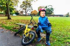 Мальчик велосипедиста при шлем безопасности отдыхая на стенде outdoors на парке осени Стоковые Фото