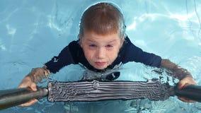 Мальчик взбираясь вверх лестница бассейна стоковое фото