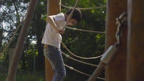 Мальчик взбираясь на оборудовании спортивной площадки сток-видео