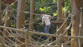 Мальчик взбираясь на оборудовании спортивной площадки видеоматериал