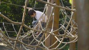 Мальчик взбираясь на оборудовании спортивной площадки акции видеоматериалы