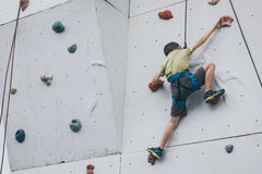 Мальчик взбираясь стена утеса внешняя Стоковое Изображение RF