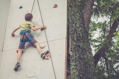 Мальчик взбираясь стена утеса внешняя Стоковое Изображение