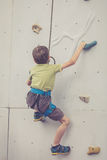 Мальчик взбираясь стена утеса внешняя Стоковые Фото