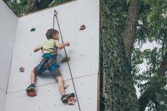 Мальчик взбираясь стена утеса внешняя Стоковая Фотография RF