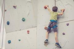 Мальчик взбираясь стена утеса внешняя Стоковые Фотографии RF