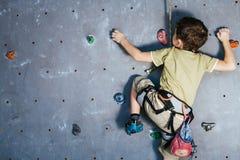Мальчик взбираясь стена утеса крытая Стоковое Фото