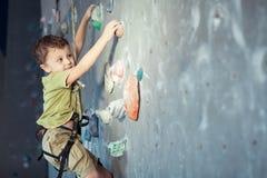 Мальчик взбираясь стена утеса крытая Стоковые Изображения RF
