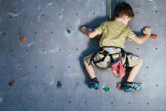 Мальчик взбираясь стена утеса крытая Стоковая Фотография RF
