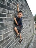 Мальчик взбираясь черная кирпичная стена Стоковые Фото