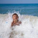 Мальчик внутри брызгает моря стоковое фото rf
