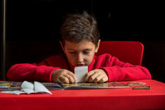 Мальчик вставляя стикеры в альбоме Стоковое Фото