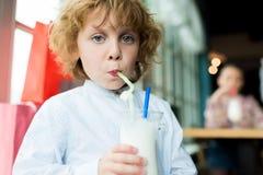 Мальчик выпивая очень вкусный milkshake от соломы в кафе Стоковые Фотографии RF