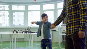 Мальчик вытягивает его отца для того чтобы сыграть с ним видеоматериал