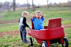 Мальчик вытягивая зевая брата в красной фуре Стоковое Изображение