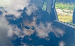 Мальчик в автомобиле с стеклами стоковые изображения