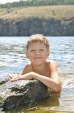 Мальчик в воде на камне Стоковые Изображения