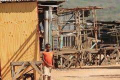Мальчик в городке хибарки стоковые изображения