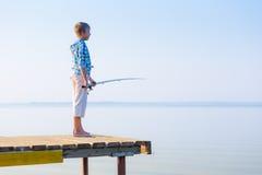 Мальчик в голубой рубашке стоя на пироге Стоковое Фото