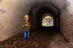 Мальчик в желтой крышке в руинах Стоковые Изображения