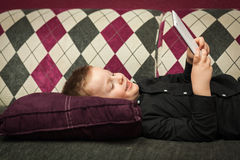 Мальчик в живущей комнате на кресле играя на таблетке Стоковое Изображение RF