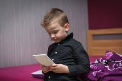 Мальчик в живущей комнате на кресле играя на таблетке Стоковые Фотографии RF
